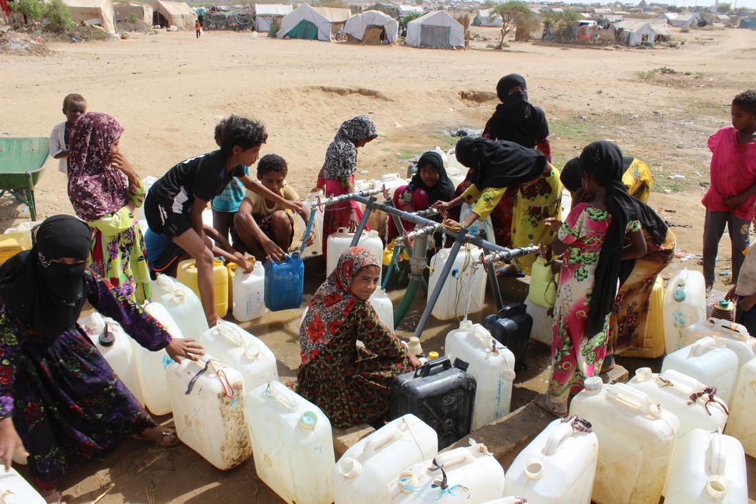 Des femmes vont à un point d'eau mis en place par Oxfam dans un camp au Yémen