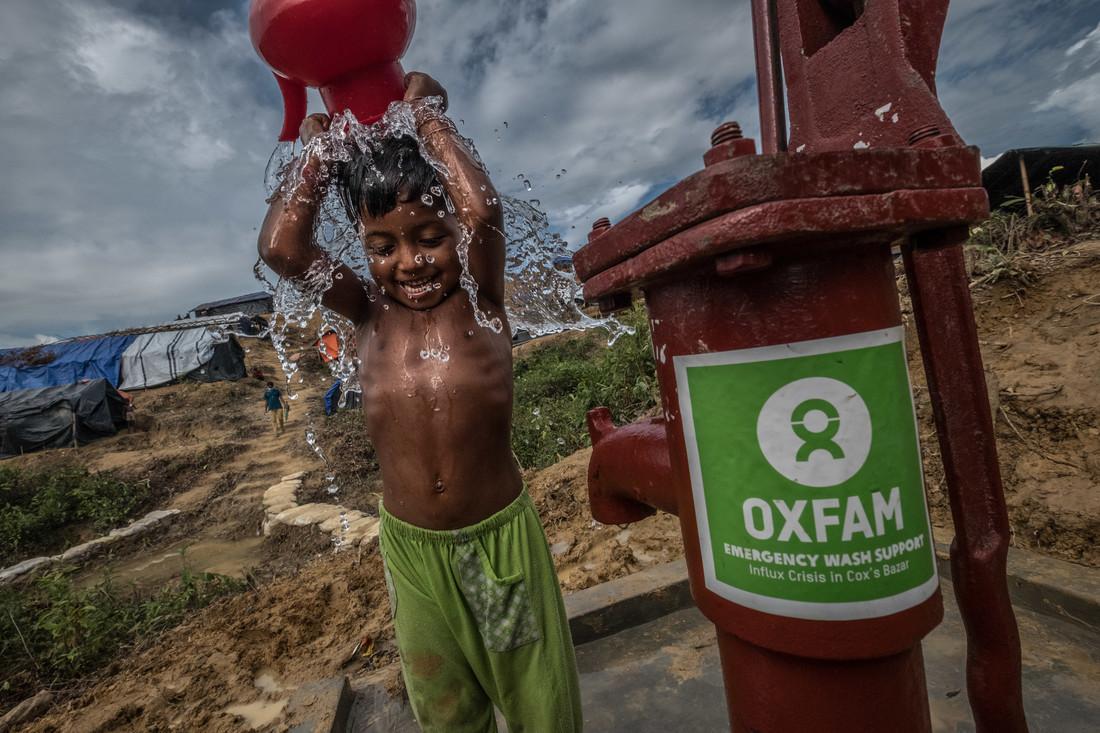 Un enfant se lave avec une installation d'eau construite par Oxfam dans le camp de réfugiés de Kutupalong